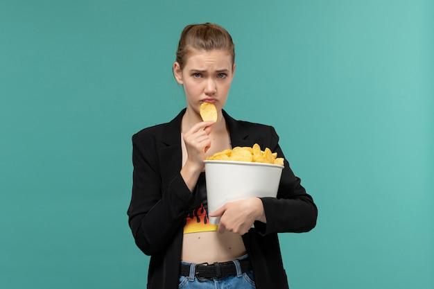 전면보기 젊은 여성 잡고 파란색 표면에 영화를보고 칩을 먹는