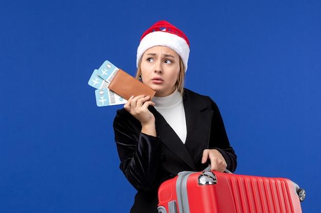 Вид спереди молодая женщина, держащая сумку и билеты на синем столе, самолет, праздничный отдых