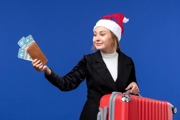 Вид спереди молодая женщина, держащая сумку и билеты на синем стенном самолете, праздничные каникулы