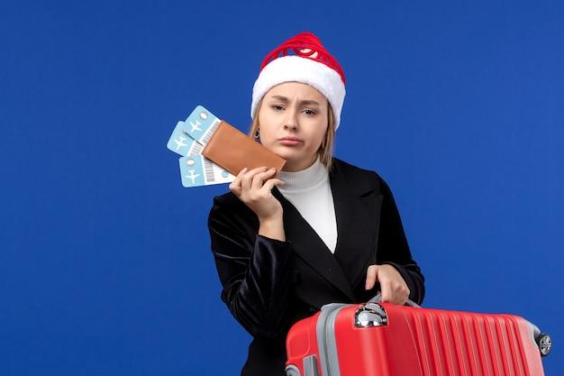 Вид спереди молодая женщина, держащая сумку и билеты на синей стене, отпуск, отпуск
