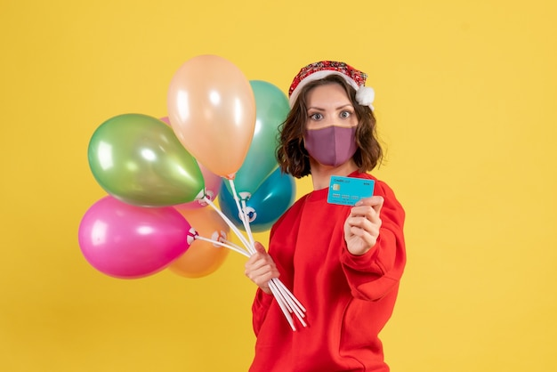 Front view young female holding balloons and bank card in mask on yellow