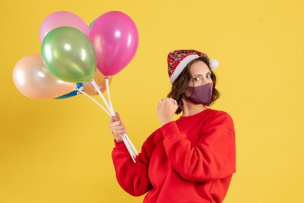 Вид спереди молодая женщина, держащая воздушные шары в стерильной маске на желтом