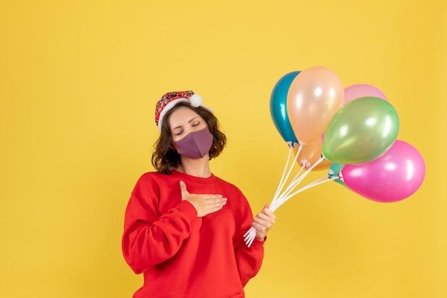 黄色の滅菌マスクでバルーンを保持している若い女性の正面図