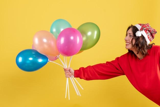 Вид спереди молодая женщина держит воздушные шары на желтом
