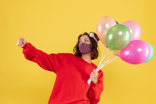 Front view young female holding balloons in sterile mask on the yellow