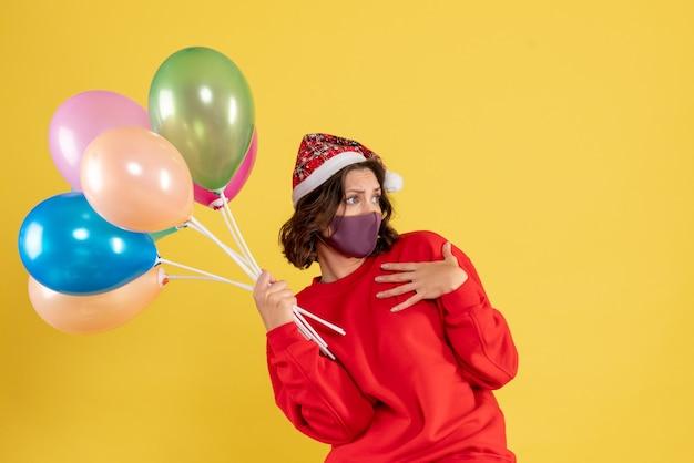 Vista frontale giovane femmina che tiene palloncini in maschera sterile su giallo