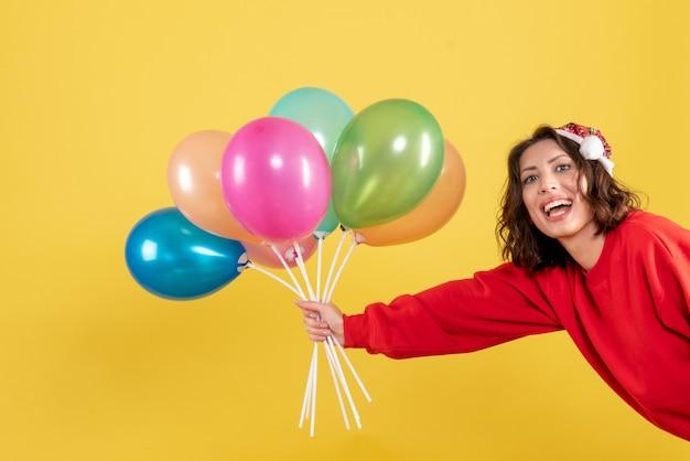 Vista frontale giovane femmina azienda palloncini su colore giallo