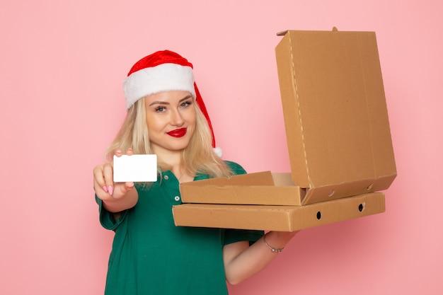 Вид спереди молодая женщина, держащая банковскую карту и коробки для пиццы на светло-розовой стене, цвет праздника, рождество, новый год, фото, рабочая форма