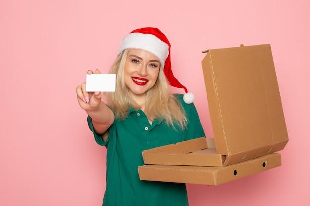 Вид спереди молодая женщина, держащая банковскую карту и коробки для пиццы на розовой стене, праздничная новогодняя фотография, рабочая форма