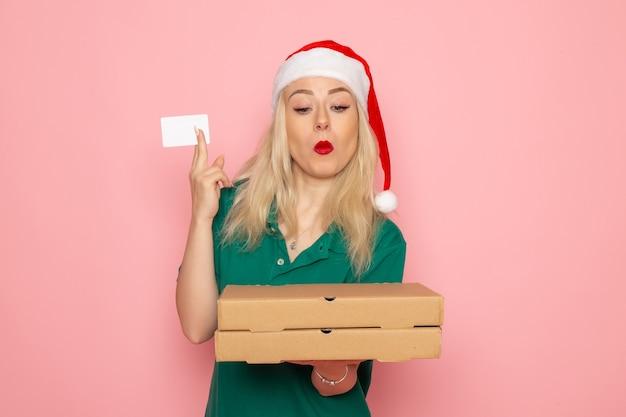 Вид спереди молодая женщина, держащая банковскую карту и коробки для пиццы на розовой стене, праздничная рождественская новогодняя рабочая форма