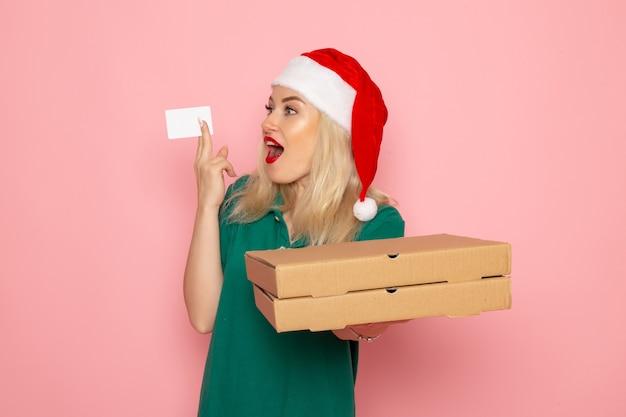 Вид спереди молодая женщина, держащая банковскую карту и коробки для пиццы на розовой стене, цветная праздничная рождественская новогодняя фото-форма