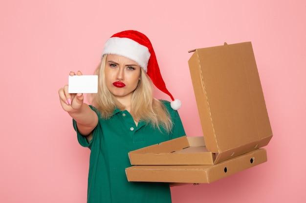 Вид спереди молодая женщина, держащая банковскую карту и коробки для пиццы на розовой стене, цвет праздников, рождество, новый год, фото, форма работы