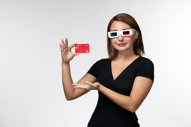Front view young female holding bank card in -d sunglasses smiling on white surface