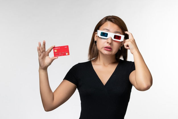 Front view young female holding bank card in d sunglasses and thinking on a white surface
