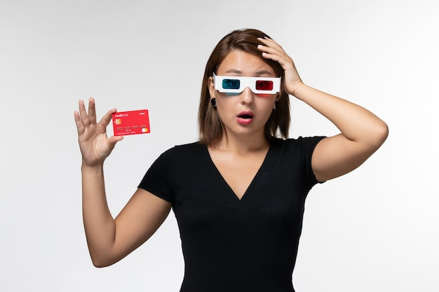 Front view young female holding bank card in d sunglasses and thinking on white surface