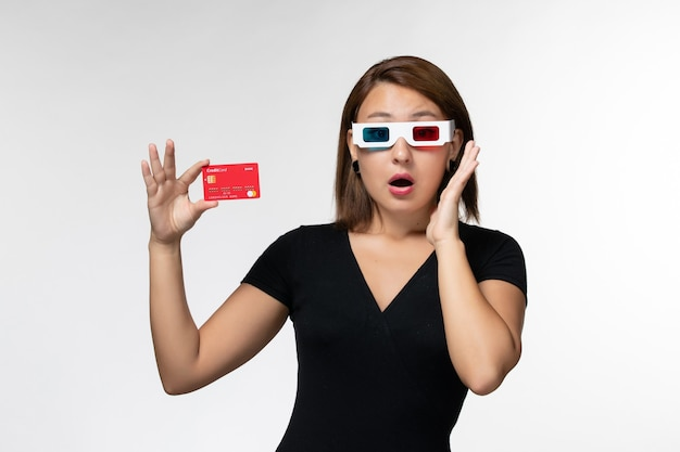 Front view young female holding bank card in -d sunglasses on a white surface