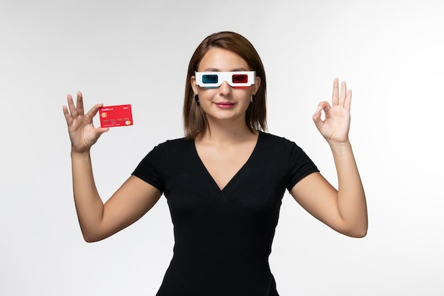 Front view young female holding bank card in -d sunglasses on the white surface
