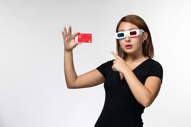 Front view young female holding bank card in -d sunglasses on white surface