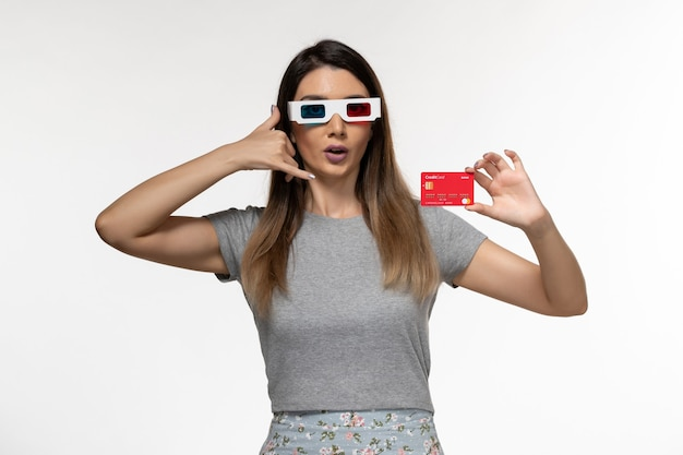 Front view young female holding bank card in d sunglasses on the white surface