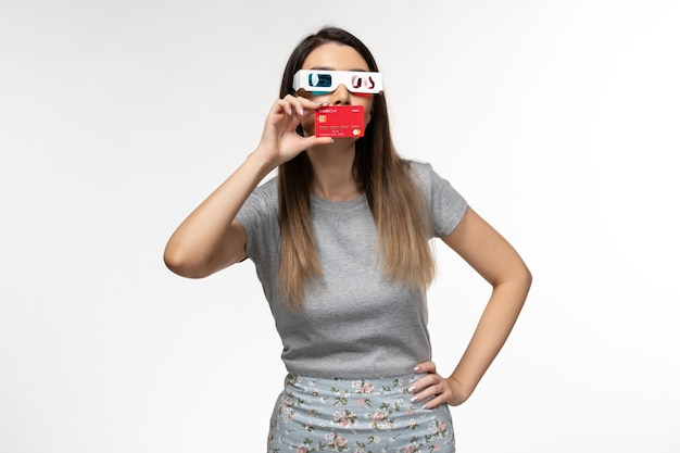 Front view young female holding bank card in d sunglasses on white surface