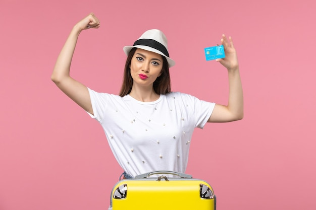 Front view young female holding bank card flexing on pink wall woman trip summer voyage