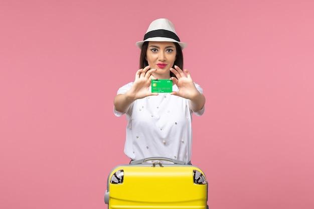Vista frontale giovane donna in possesso di carta di credito sulla parete rosa chiaro emozione viaggio estivo woman