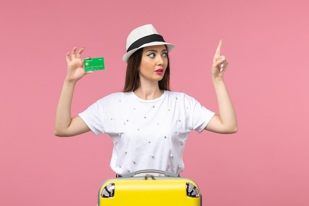 Front view young female holding bank card on light-pink wall emotion summer woman trip
