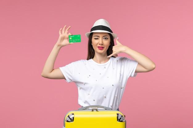 Vista frontale giovane donna in possesso di carta di credito sulla parete rosa chiaro viaggio estivo emozione woman