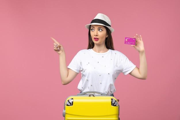 Vista frontale giovane donna in possesso di carta di credito su muro rosa chiaro viaggio donna vacanza soldi