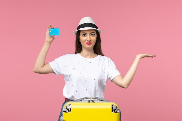 Front view young female holding bank card on light pink wall woman trip summer emotion