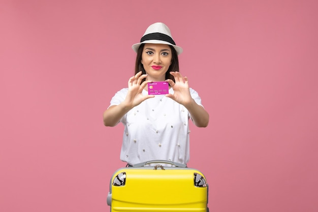 Вид спереди молодая женщина, держащая банковскую карту на розовом столе, поездка, деньги, цвет, отпуск
