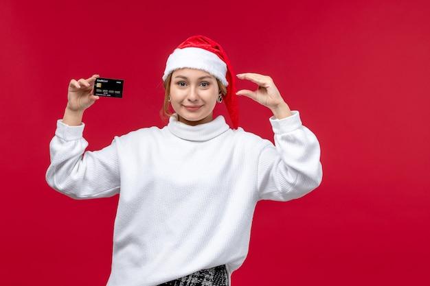 Вид спереди молодая женщина, держащая банковскую карту на светло-красном фоне