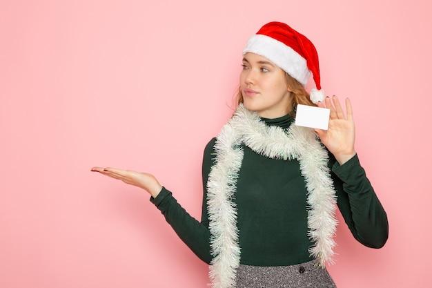 ピンクの壁のモデルの休日のクリスマスの新年の感情に銀行カードを保持している若い女性の正面図