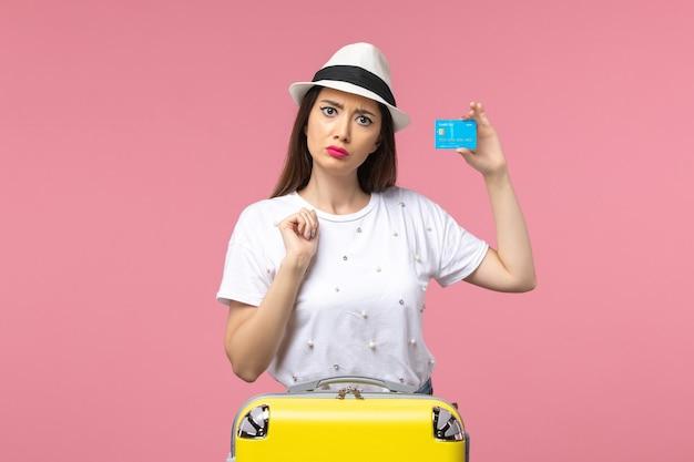 Вид спереди молодая женщина, держащая банковскую карту на розовой стене, женщина, поездка, летние эмоции