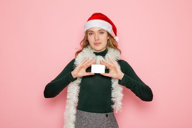 Vista frontale giovane femmina in possesso di carta bancaria sul muro rosa modello vacanza natale