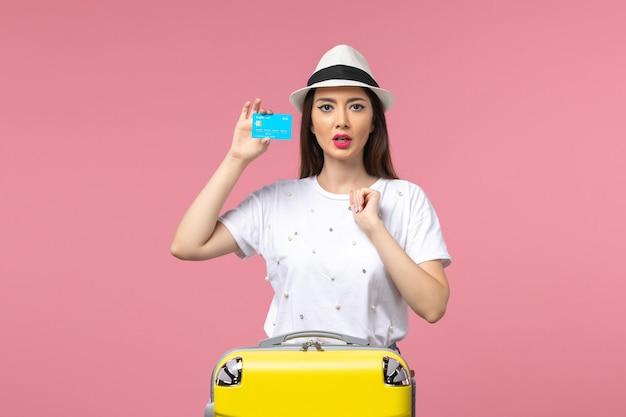 Vista frontale giovane donna in possesso di carta di credito sulla parete rosa estate viaggio emozione woman