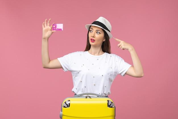 Vista frontale giovane donna in possesso di carta di credito sulla parete rosa viaggio denaro colore vacanza