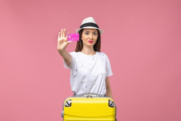 Vista frontale giovane donna in possesso di carta di credito sulla parete rosa viaggio soldi colori vacanza
