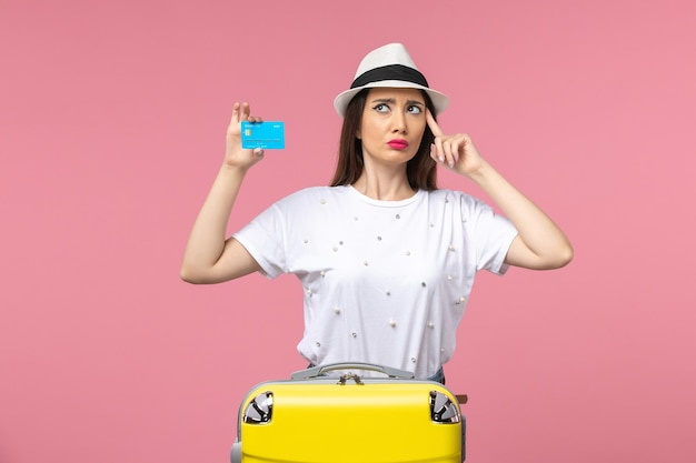 Front view young female holding bank card on a pink wall trip woman summer emotions