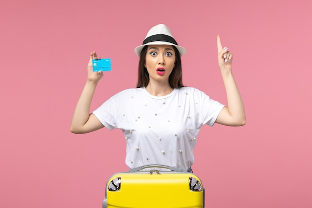 Front view young female holding bank card on the pink wall trip woman summer emotions