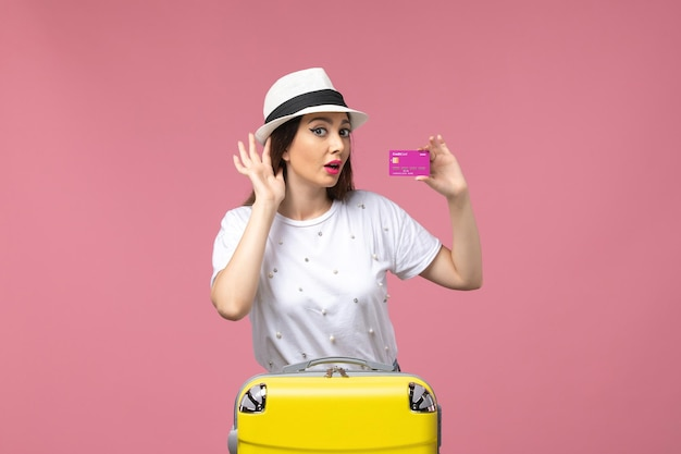 Vista frontale giovane donna in possesso di carta di credito sul muro rosa vacanza donna viaggio soldi