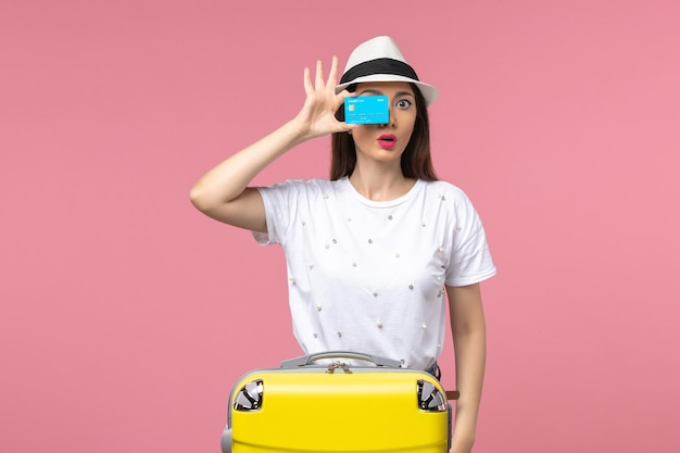 Vista frontale giovane donna in possesso di carta di credito sul muro rosa donna viaggio viaggio estivo