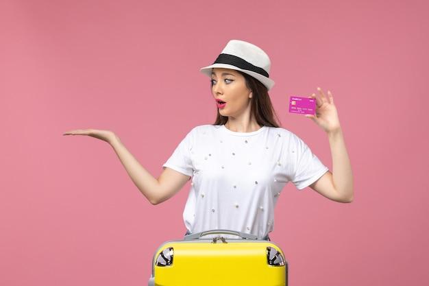 Vista frontale giovane donna in possesso di carta di credito sul muro rosa donna vacanza soldi viaggio