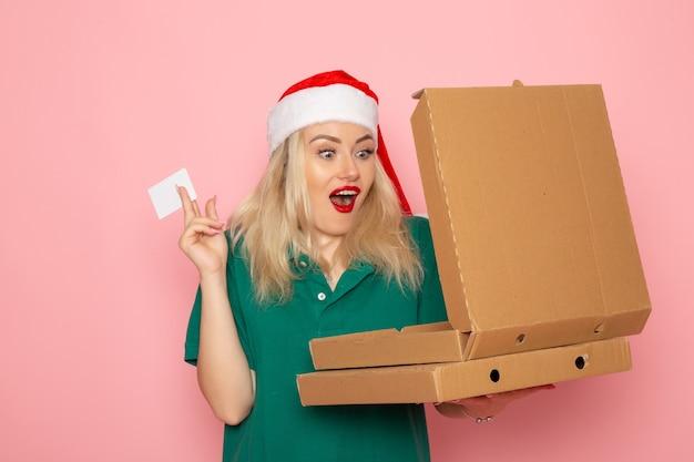 Vista frontale giovane femmina in possesso di carta bancaria e scatole per pizza sulla parete rosa colore vacanza natale capodanno foto uniforme