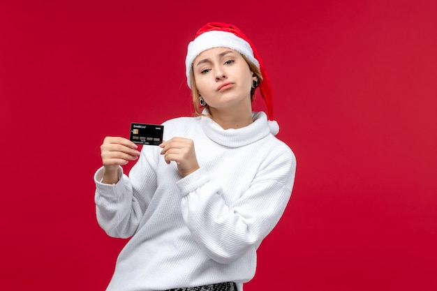 Front view young female holding bank card on a red background