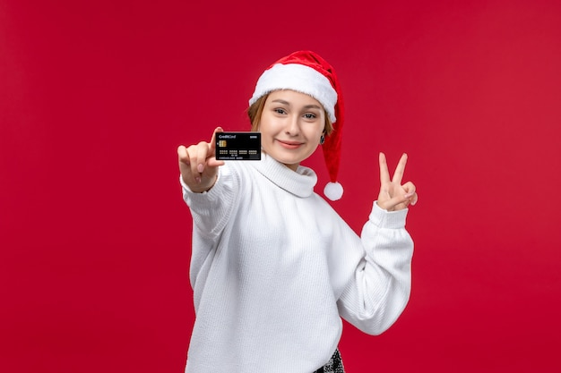 Front view young female holding bank card on red background
