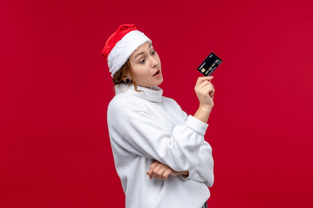 Front view young female holding bank card on the red background