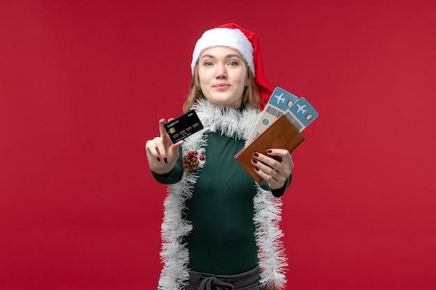 Вид спереди молодая женщина, держащая билеты по банковской карте на красном фоне