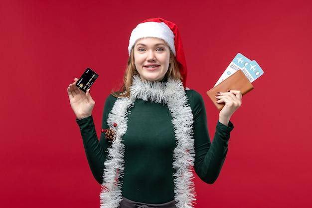Giovane femmina di vista frontale che tiene i biglietti della carta di credito sullo scrittorio rosso