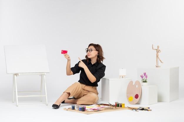 Vista frontale giovane donna che tiene carta di credito su sfondo bianco white